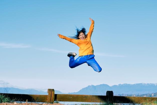 Mujer joven con un estilo hip-hop está saltando en un espacio natural Foto Premium