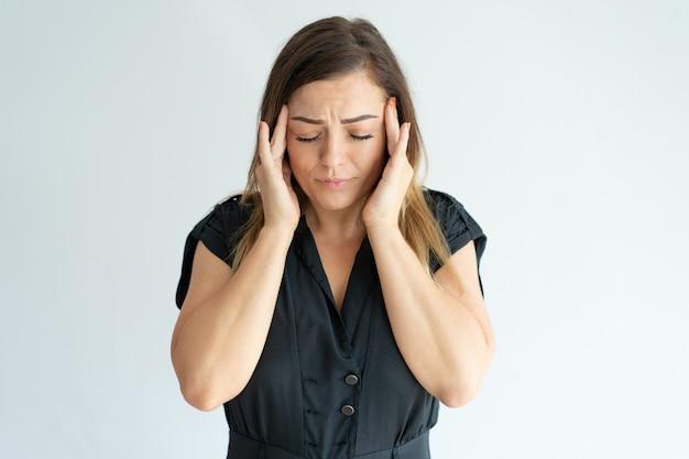 Mujer joven estresada cansada en alineada negra que siente dolor de cabeza y que da masajes a templos. Foto gratis