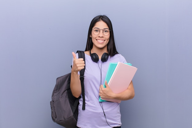 Mujer joven estudiante bastante latino contra la pared gris Foto Premium