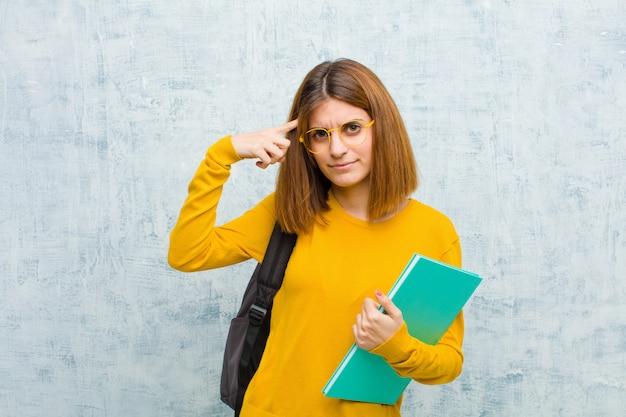 Mujer joven estudiante que se siente confundida y perpleja, mostrando que estás loco, loco o fuera de tu mente. Foto Premium