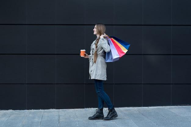 Mujer joven feliz con bolsas de colores y taza de papel. Foto Premium