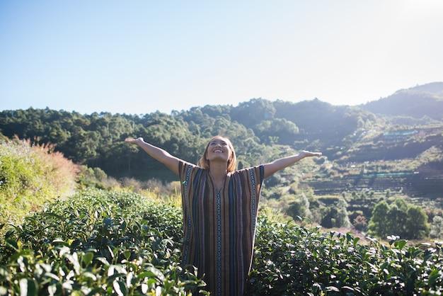 Mujer joven feliz en la plantación de té Foto gratis