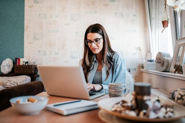 Mujer joven feliz que estudia en la computadora portátil en su apartamento. Foto Premium