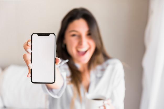 Mujer joven feliz que muestra el teléfono móvil de la pantalla blanca Foto gratis