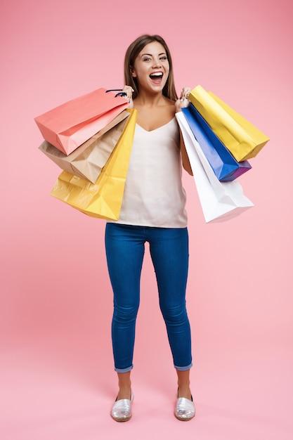 Mujer joven feliz que sostiene bolsos de compras quedándose en la pared rosada Foto gratis