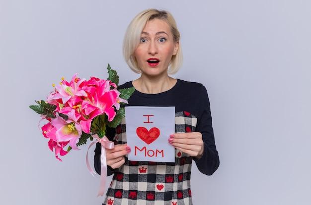 Mujer joven feliz y sorprendida en un hermoso vestido con tarjeta de felicitación y ramo de flores mirando al frente celebrando el día de la madre de pie sobre la pared blanca Foto gratis