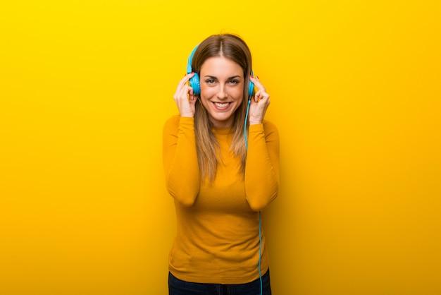 Mujer joven en fondo amarillo que escucha la música con los auriculares Foto Premium
