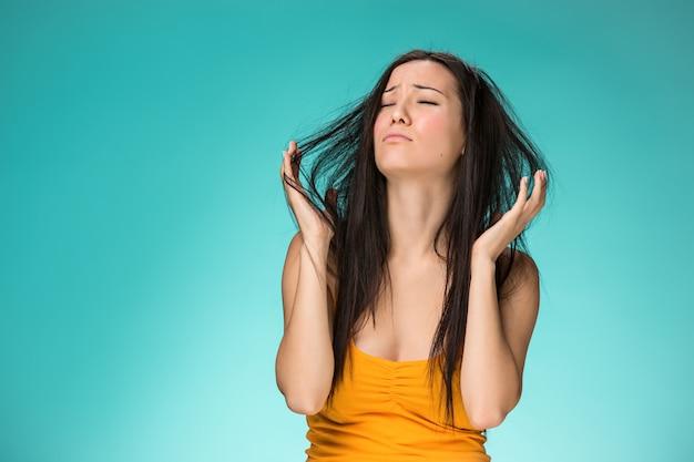 Mujer joven frustrada que tiene un mal cabello Foto gratis