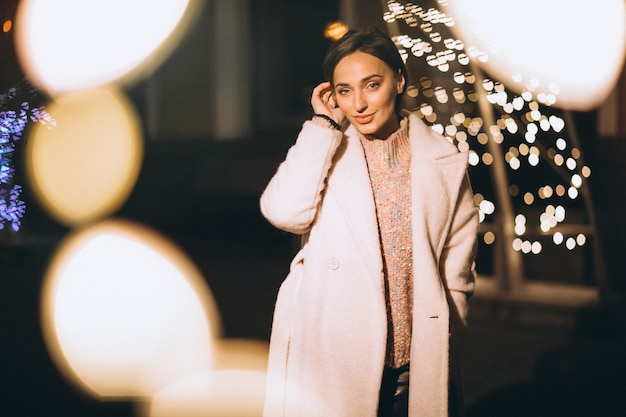 Mujer joven fuera de la calle de noche con luces Foto gratis