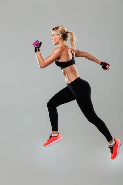Mujer joven fuerte de los deportes que se ejecuta aislada Foto gratis