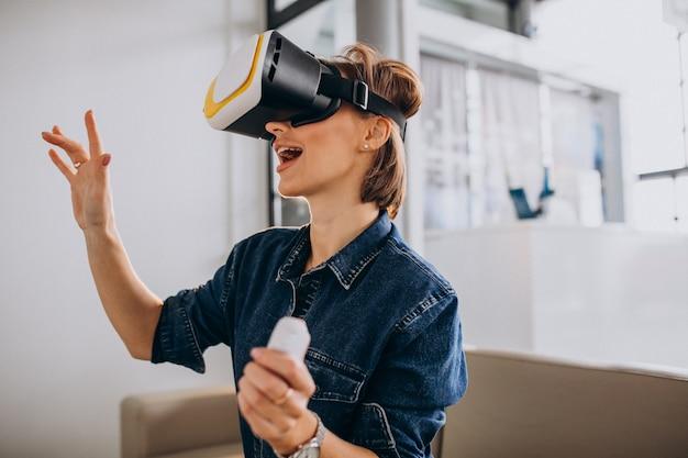 Mujer joven con gafas de realidad virtual y jugando juegos virtuales con control remoto Foto gratis