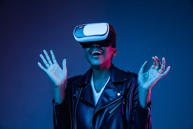 Mujer joven con gafas de realidad virtual con luces de neón Foto gratis