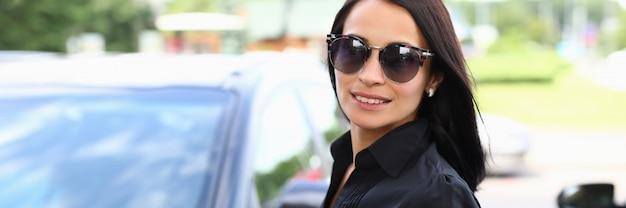 Mujer joven con gafas de sol se encuentra cerca de un coche negro en un aparcamiento. pruebe la conducción antes de comprar un automóvil. entrenamiento de manejo Foto Premium