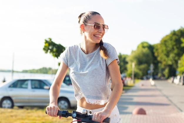 Mujer joven con gafas de sol en scooter Foto gratis