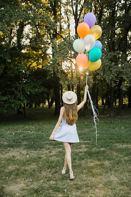 Mujer joven con globos al aire libre Foto gratis