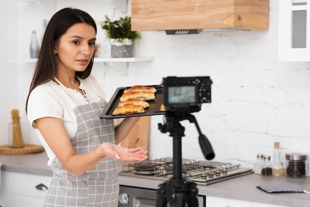 Mujer joven grabando para un show de cocina Foto gratis