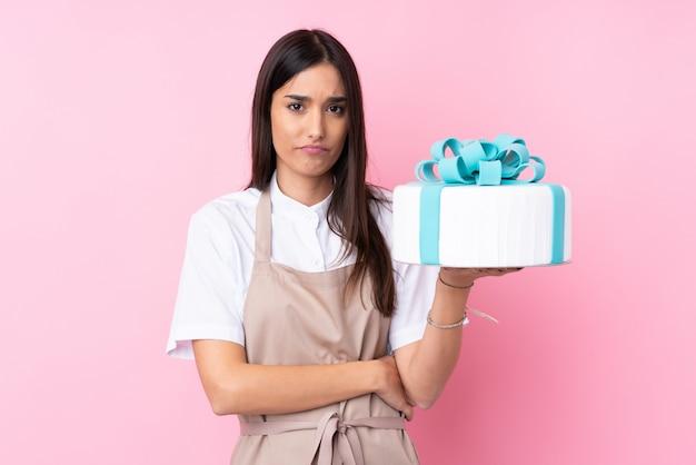 Mujer joven con un gran pastel sobre pared aislada con expresión triste Foto Premium