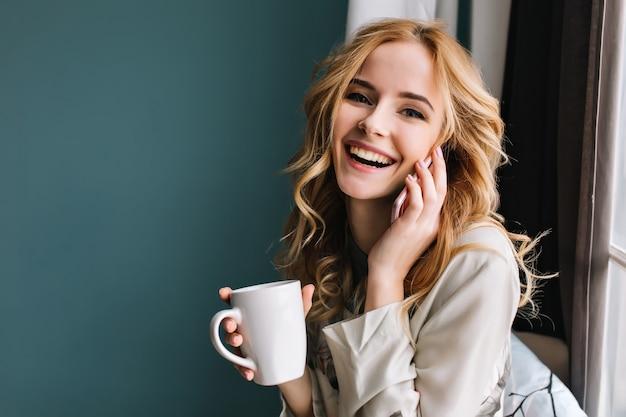 Mujer joven hablando por teléfono y riendo con una taza de café, té en la mano, feliz mañana. ella tiene un hermoso cabello rubio ondulado. habitación con pared azul turquesa. usando un bonito pijama de encaje. Foto gratis