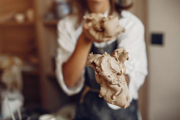 Mujer joven hace cerámica en taller Foto gratis
