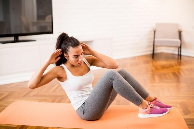 Foto Premium | Mujer joven haciendo ejercicio de abs en la habitación