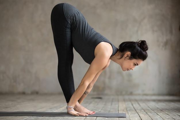 Mujer joven haciendo ejercicio de ardha uttanasana