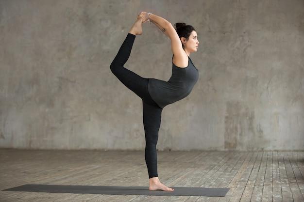 Mujer joven haciendo ejercicio de natarajasana Foto gratis