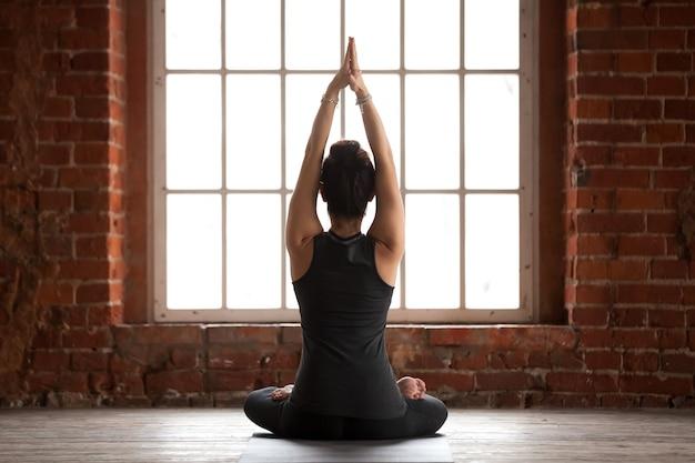 Mujer joven haciendo ejercicio sukhasana, vista trasera Foto gratis