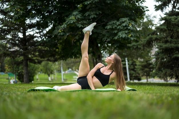 Mujer joven haciendo ejercicios tiro largo Foto gratis