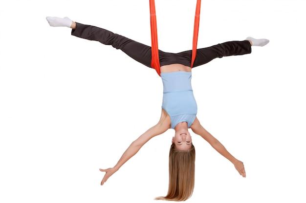 Mujer joven haciendo ejercicios de yoga antigravedad en estiramiento de hilo Foto gratis