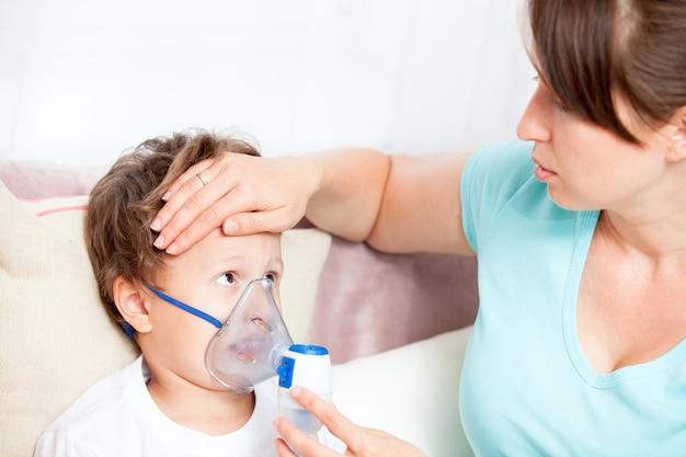 Mujer joven haciendo inhalación con un hijo nebulizador y toca su frente Foto Premium