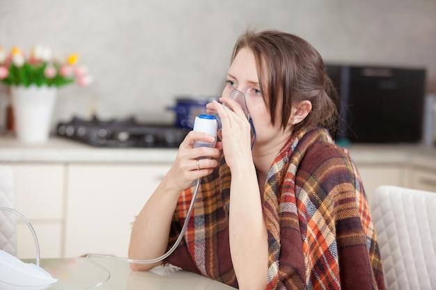 Mujer joven haciendo inhalación con un nebulizador en casa Foto Premium