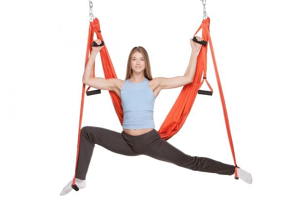 Mujer joven haciendo yoga aéreo antigravedad en hamaca sobre un blanco transparente Foto gratis