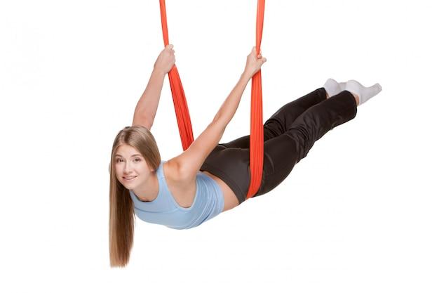 Mujer joven haciendo yoga aéreo antigravedad Foto gratis