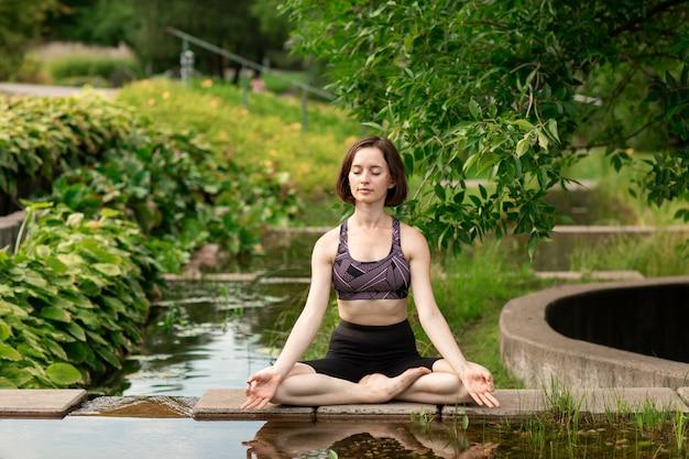 Mujer joven haciendo yoga. niña sentada en posición de loto en el parque cerca de un pequeño lago decorativo Foto Premium