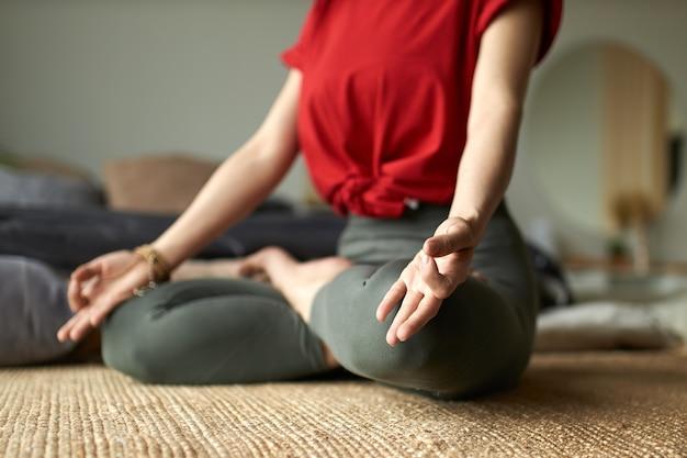 Mujer joven haciendo yoga en posición de loto en casa Foto gratis