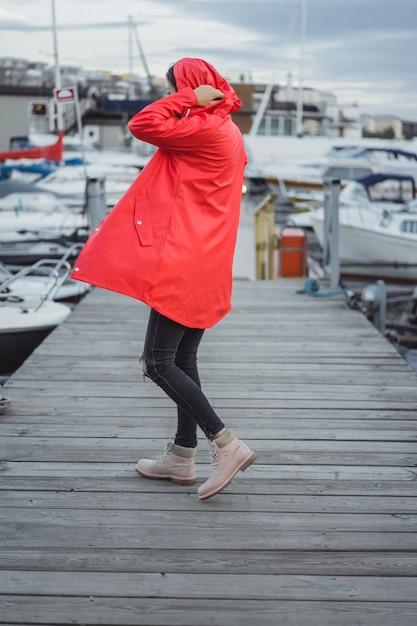 Mujer joven hermosa en una capa roja en el puerto del yate. estocolmo, suiza Foto gratis