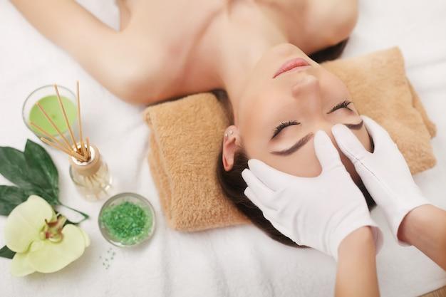Mujer joven hermosa que consigue masaje facial que miente en el sofá. vista superior enfocada en la cara Foto Premium