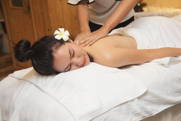 Mujer joven hermosa que consigue el salón del masaje del balneario y la flor blanca en su oído. Foto Premium