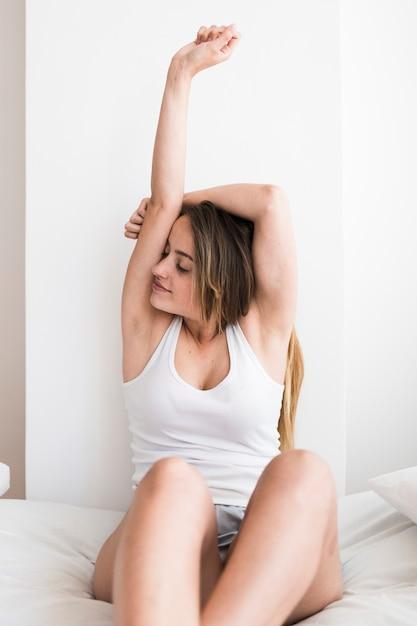 Mujer joven hermosa que estira sus brazos en cama Foto gratis