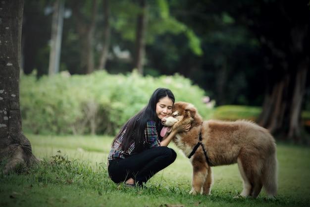 Mujer joven hermosa que juega con su pequeño perro en un parque al aire libre. retrato de estilo de vida Foto gratis