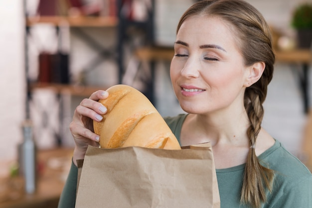 Mujer joven hermosa que sostiene el pan fresco Foto gratis