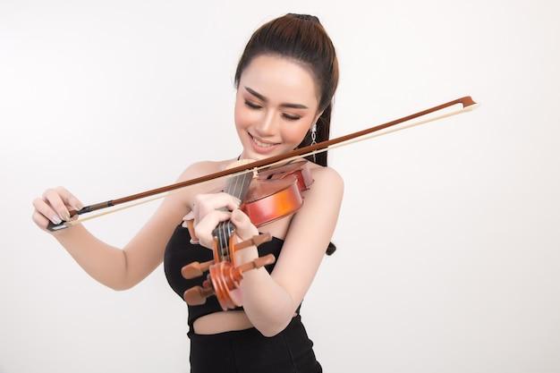 Mujer joven hermosa que toca el violín sobre el fondo blanco Foto gratis