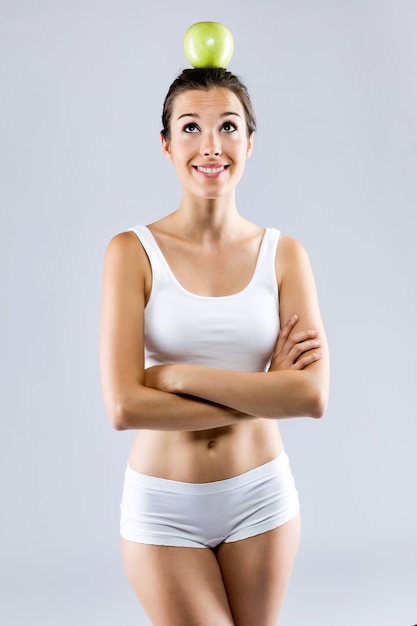 Mujer joven hermosa en la ropa interior blanca que sostiene la manzana verde.   e8a92793c401