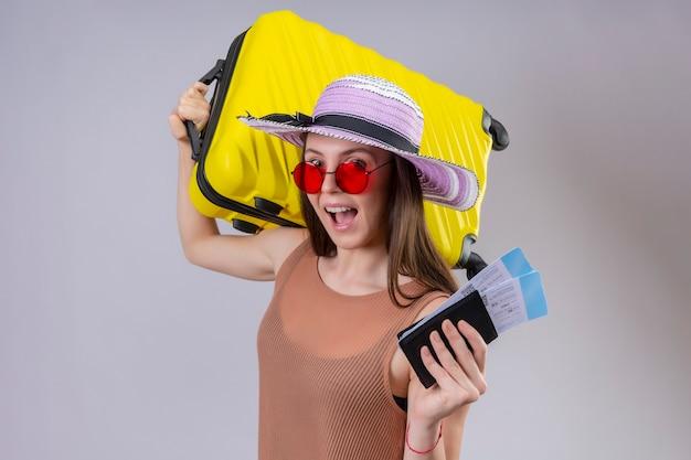 Mujer joven hermosa viajera con sombrero de verano con gafas de sol rojas con maleta amarilla y billetes de avión sonriendo alegremente con cara feliz de pie sobre fondo blanco. Foto gratis