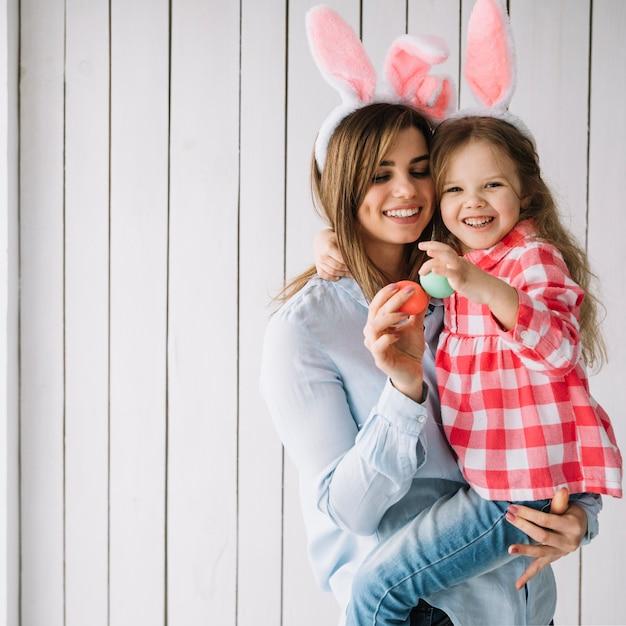 Mujer joven con hija en brazos con huevos de pascua Foto gratis