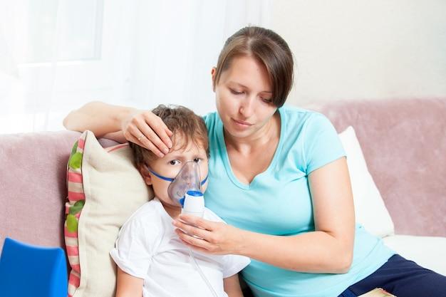 Mujer joven con hijo haciendo inhalación con un nebulizador en casa y leer un libro Foto Premium