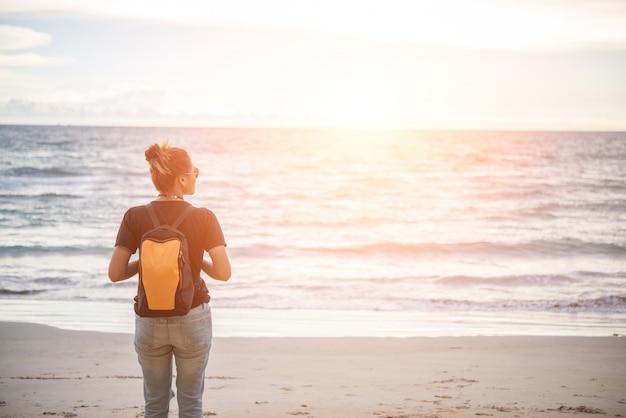 12a2db823 Mujer joven hipster con mochila de pie por la playa. | Descargar ...