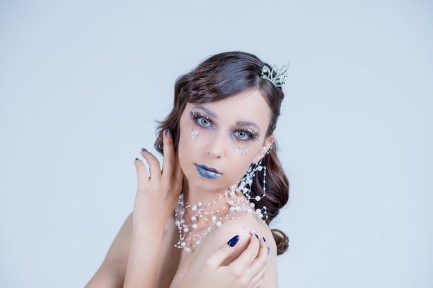 Mujer joven en imagen creativa con plata maquillaje artístico. rostro de mujer hermosa. Foto Premium