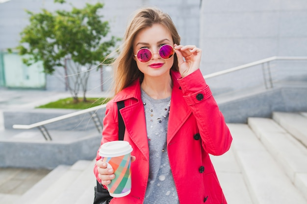 Mujer joven inconformista en abrigo rosa, jeans en la calle con mochila y café escuchando música en auriculares, con gafas de sol Foto gratis