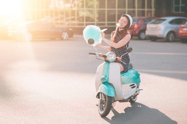 Mujer joven inconformista feliz comiendo algodón de azúcar endulzado. modelo femenino montando un scooter azul una calle de la ciudad. Foto Premium